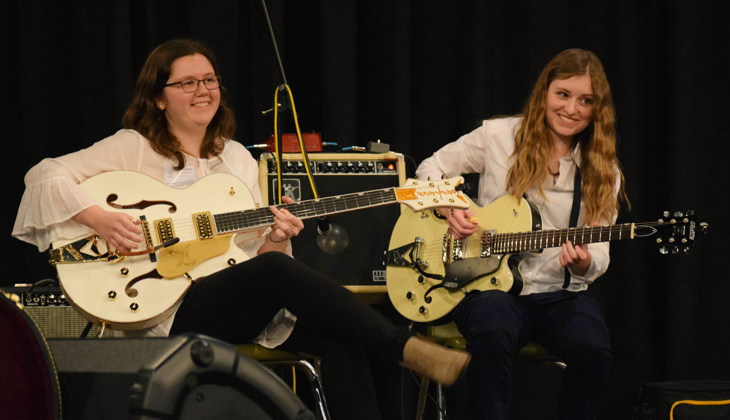 Katelyn Prieboy (left) and Bella Speelman playing their new Gretsch guitars onstage at the International Home of the Legends Thumbpicking Competition in Powderly, Ky.